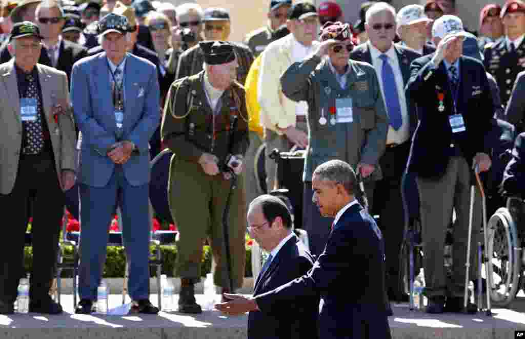 U.S. President Barack Obama and French President Francois Hollande walk by veterans and participants at a D-Day ceremony at the Normandy American Cemetery and Memorial in Colleville-sur-Mer, France, June 6, 2014.