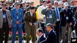 Presiden AS Barack Obama dan Presiden Perancis Francois Hollande berjalan melewati barisan para veteran dan hadirin dalam peringatan 70 tahun invansi D-Day di Taman Makam Pahlawan dan Tugu peringatan Normandia-Amerika di Colleville-sur-Mer (6/6).