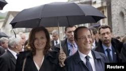 法国总统奥朗德(右)和他多年伴侣瓦莱丽•特里耶韦莱(左)2012年6月9日在法国西南部城镇参加二战纪念仪式的照片。