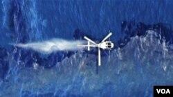 Helikopter menyempotkan dispersan di atas tumpahan minyak kapal kargo Rena yang terjebak di terumbu karang Tauranga, Selandia Baru (foto:dok).