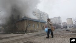 A woman resident passes by a burning house in Mariupol, Ukraine, Saturday, Jan. 24, 2015.