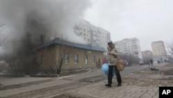 一名婦人走過烏克蘭城市馬里烏伯爾的居民區遭火箭彈襲擊的建築。
