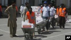 Para relawan membagikan bantuan bahan pangan kepada fakir miskin saat penerapan lockdown Covid-19 pada bulan Ramadan di Peshawar, Pakistan (4/5).
