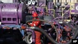 Pekerja di operasi perekahan hidrolik di sumur minyak Encana, negara bagian Colorado. (AP/Brennan Linsley)