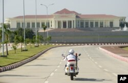 FILE - A police motorcycle approaches the President's Office in Naypyidaw, Myanmar, Dec. 1, 2011.