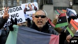 Người Libya sống ở Cộng hòa Czech cầm biểu ngữ, cờ quốc gia cũ của Libya, hô khẩu hiệu chống ông Gadhafi và lên án các vụ đàn áp đẫm máu nhắm vào người biểu tình, ngày 25/2/2011