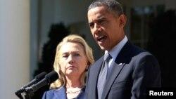 Başkan Barack Obama, Beyaz Saray'daki açıklamasını yaparken arkasında bekleyen Hillary Clinton