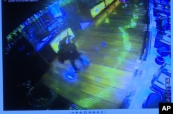This image taken from TV of CCTV video shows a gunman firing a weapon into the air inside a casino in the Resorts World Manila complex before starting fires and firing on security forces, June 2, 2017. Philippine police say the attacker was a tall, English-speaking man with a mustache.