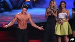 Zac Efron acepta el premio a la mejor actuación sin camisa. Atrás, observan Rita Ora and Jessica Alba.