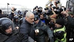 3月18号,俄罗斯警察在莫斯科NTV电视台外面拘留一名反对派人士。
