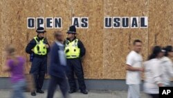 Police officers from Wales patrol outside a boarded up shop in Streatham, south London, August 10, 2011