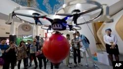 Du khách đến hội chợ triển lãm để xem máy bay không người lái được điều khiển bằng điện thoại di động ở Bắc Kinh ngày 24/4/2015.