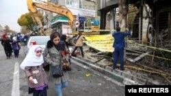 ປະຊາຊົນຍ່າງໃກ້ທະນາຄານທີ່ຖືກໄຟໃໝ້ ຫຼັງຈາກການປະທ້ວງຕໍ່ຕ້ານການຂຶ້ນລາຄານ້ຳມັນໃນນະຄອນຫຼວງ ເຕຫະຣ່ານ. ພະຈິກ 20, 2019. Nazanin Tabatabaee/WANA (West Asia News Agency) via REUTERS ATTENTION EDITORS - THIS IMAGE…