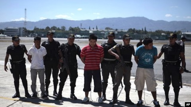 Guatemalan police escort suspected members of the Zetas drug cartel at the air force base in Guatemala City, March 8, 2012.