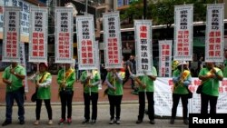 Những người ủng hộ Hội Thanh Niên Quan Ái biểu tình chống Pháp Luân Công tại một khu mua sắm ở Hồng Kông, ngày 7/6/2014.