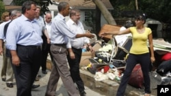 President Barack Obama walks with New Jersey Gov. Chris Christie in Wayne, N.J., Sunday, Sept. 4, 2011, as he tours flood damage caused by Hurricane Irene.