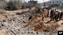 Cư dân Palestine kiểm tra thiệt hại sau vụ không kích của Israel vào Dải Gaza, ngày 24/6/2013.