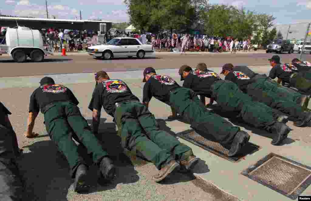 A wildland firefighting crew does 19 push-ups next to a memorial in honor of the 19 firefighters killed in the nearby wildfire in Prescott, Arizona, July 8, 2013.