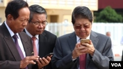 Senior Cambodian government officials are using their smart phones while awaiting the return of Cambodian Prime Minister Hun Sen from France at Phnom Penh International Airport, October 28, 2015. Government officials and state institutions have recently taken to Facebook to inform the public as the social media platform is becoming increasingly popular among Cambodian youth. (Hean Socheata/VOA Khmer)