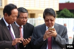 Senior Cambodian government officers are using their smart phones while awaiting the return of Cambodian Prime Minister Hun Sen from France at Phnom Penh International Airport, October 28, 2015.
