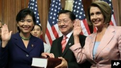 Rep. Judy Chu, D-Calif., left, re-enacts a swearing-in ceremony administered by House Speaker Nancy Pelosi July 16, 2009, in Washington. Chu's husband, Mike Eng, observes.