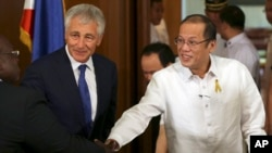 Philippine President Benigno Aquino III, right, shakes hands beside U.S. Defense Secretary Chuck Hagel, center, during his visit at the Malacanang Presidential Palace in Manila, Philippines, Aug. 30, 2013.