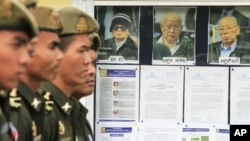 Cambodian military officials line up in front the top leaders of Khmer Rouge portraits, from right, former Khmer Rouge Foreign Minister Ieng Sary, former Khmer Rouge head of state Khieu Samphan, and former Deputy Secretary Nuon Chea, during the trial of