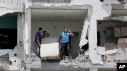 Palestinians salvage their belongings from the rubble in Beit Lahiya, northern Gaza Strip, Aug. 4, 2014.