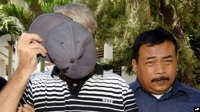 Australian Paul Francis Callahan, left, wanted in Australia and detained in Bali after being accused of child sex abuse, covers his face prior to his trial at a court in Denpasar (File Photo)