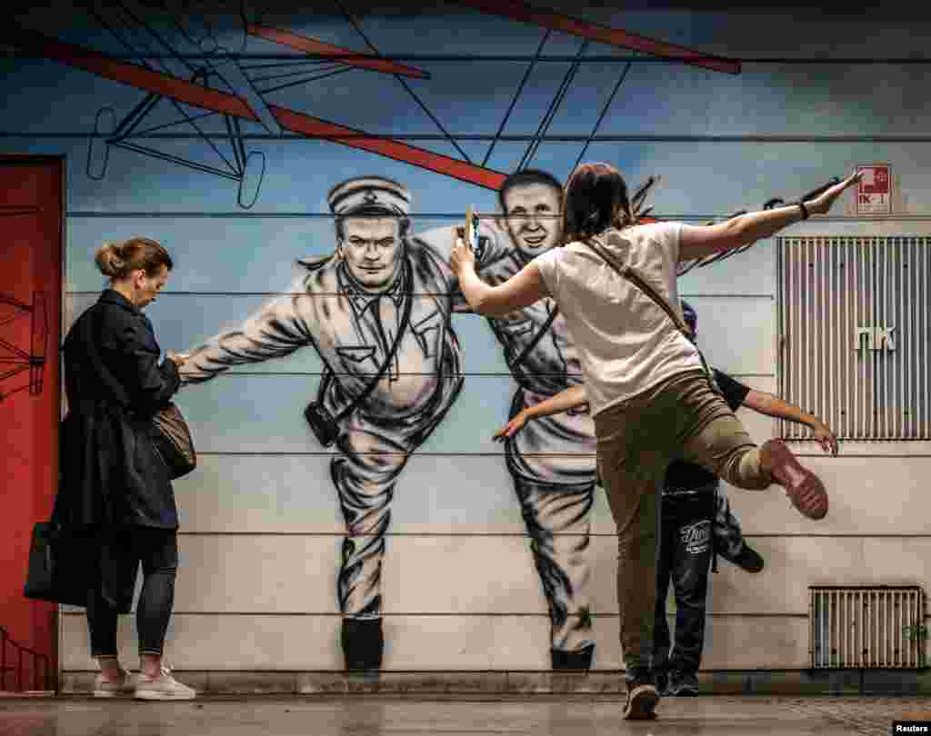 A woman and a boy pose for pictures at Chkalovskaya metro station in Moscow, Russia, in front of a mural depicting Soviet pilot Valery Chkalov - who took a non-stop flight over the Arctic and landed in the U.S. state of Washington in 1937.