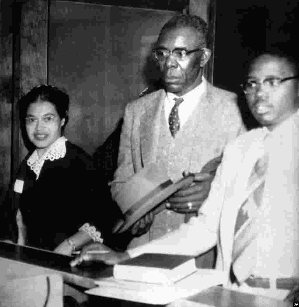 FILE - Rosa Parks, left, who was fined $10 and court costs for violating Montgomery's segregation ordinance for city buses, makes bond for appeal to Circuit Court, Dec. 5, 1955.