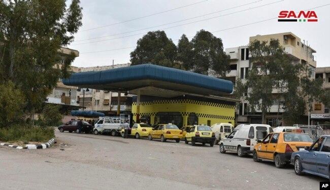 На этом фото, опубликованном 7 апреля 2019 года сирийским официальным информационным агентством SANA, изображены автомобили, стоящие в очереди для заправки топливом в своих баках, на заправочной станции в Дараа на юге Сирии.