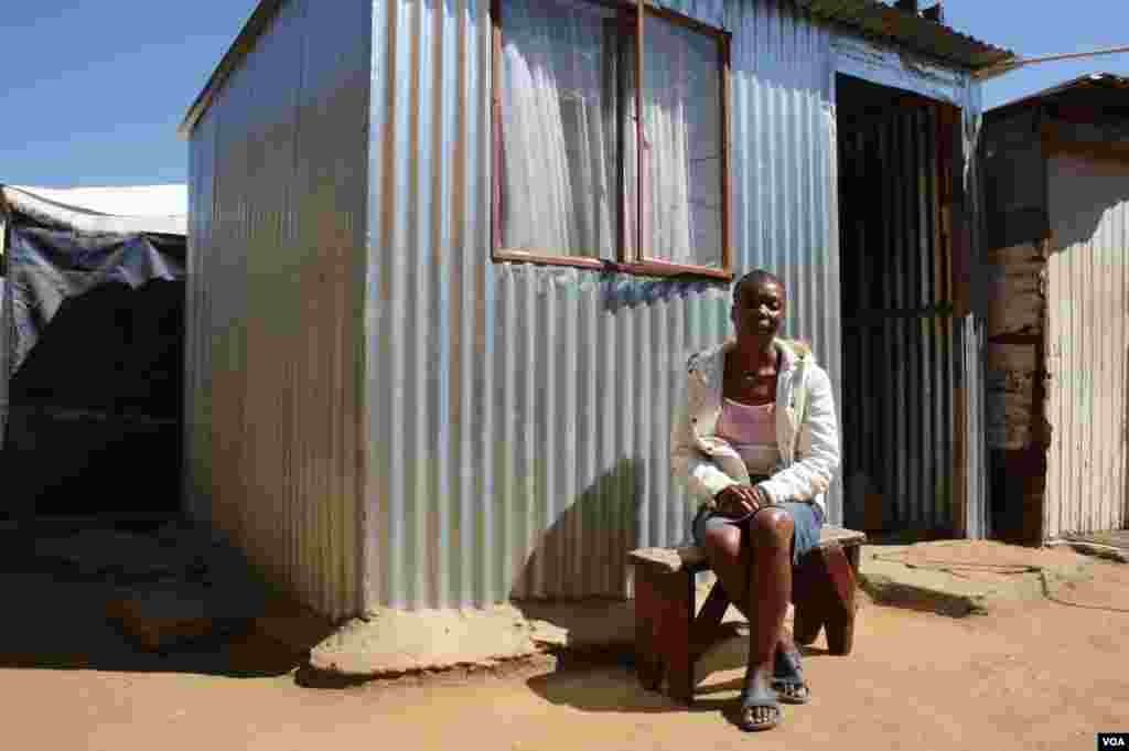 "Maureen Mabuza experienced a ""mirculous recovery"" with anti-retroviral treatment. She sits in front of her one-room shack. (Photo by Darren Taylor)"