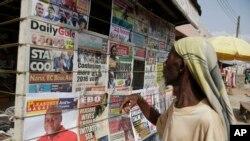 Un homme regarde les journaux locaux dans une rue d'Accra, au Ghana, le 9 décembre 2016. (AP Photo/Sunday Alamba)
