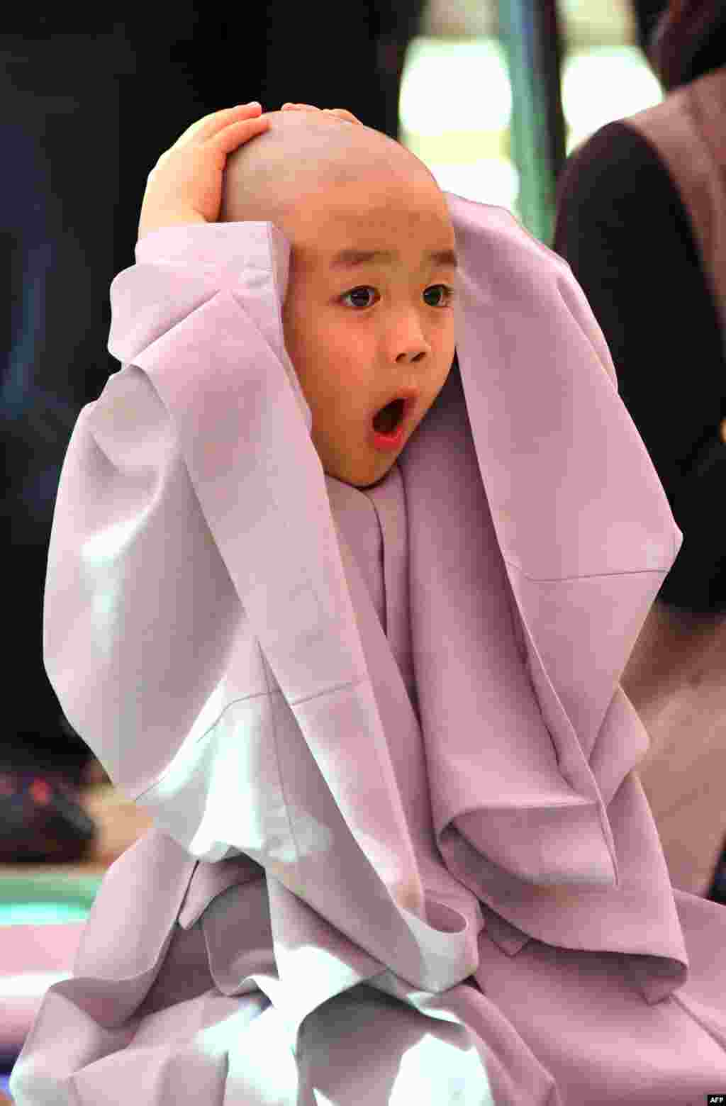 A child reacts after having his head shaved by Buddhist monks during a ceremony entitled 'Children Becoming Buddhist Monks', at the Jogye temple in Seoul, South Korea.