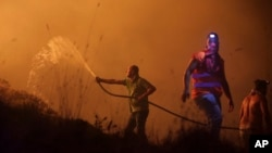 Volunteers use a water hose to fight a wild fire raging near houses in the outskirts of Obidos, Portugal, in the early hours of Oct. 16 2017.