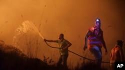 Relawan menggunakan selang air untuk melawan api liar yang berkecamuk di dekat rumah-rumah di pinggiran Obidos, Portugal, pada dini hari 16 Oktober 2017.