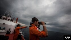 FILE - Indonesian national rescue personnel conduct search for missing Malaysia Airlines flight MH370, Andaman Sea, March 15, 2014.