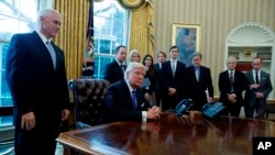 El presidente Donald Trump acompañado por el vicepresidente Mike Pence, y en espera los reporteros, antes de la firma de una orden ejecutiva en el oleoducto Keystone XL pipeline, el 24 de enero.