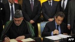 Tổng thống Pháp Nicolas Sarkozy (phải) và Tổng thống Afghanistan Hamid Karzai ký hiệp định hợp tác và hữu nghị tại Điện Élysée ở Paris hôm 27/1/12