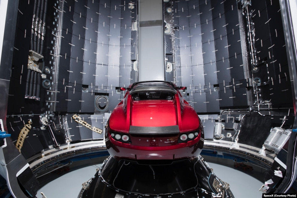 SpaceX公司提供的2017年12月6日的照片顯示,在美國佛羅里達州卡納維拉爾角,一架獵鷹重型火箭的整流罩旁邊有一輛特斯拉汽車。 獵鷹重型火箭的首次飛行,攜帶航天器和特斯拉的跑車。 在美中關稅之戰中, 中國對包括特斯拉在內的一些公司產品徵收25%的關稅。 為了平衡這次關稅增加,特斯拉提升了它在中國市場的汽車售價。 去年,中國市場上銷售的載人電能車輛增加了82%,達到47萬輛,是美國同期銷售量的兩倍。
