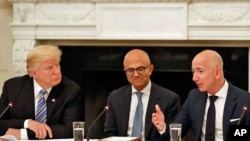 President Donald Trump, left, and Satya Nadella, Chief Executive Officer of Microsoft, center, listen as Jeff Bezos, Chief Executive Officer of Amazon, speaks during an American Technology Council roundtable in the State Dinning Room of the White House.