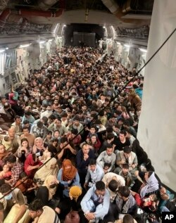 Afghan citizens pack inside a U.S. Air Force C-17 Globemaster III, as they are transported from Hamid Karzai International Airport in Afghanistan, Sunday, Aug. 15, 2021.