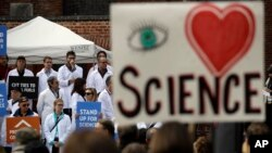 FILE - People hold signs as they listen to a group of scientists speak during a rally in conjunction with the American Geophysical Union's fall meeting Dec. 13, 2016, in San Francisco. The rally was to call attention to the issue of climate change and its