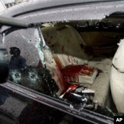 A Pakistani cameraman films the blood-stained damaged car of slain Pakistan's government minister for religious minorities Shahbaz Bhatti outside the emergency ward of a local hospital in Islamabad, Pakistan on Wednesday, March 2, 2011. Gunmen shot and ki