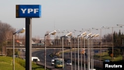 FILE - A sign of state-run energy company YPF is seen alongside a road in Buenos Aires, Aug. 28, 2014.