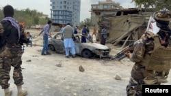阿富汗人在喀布爾拍攝一輛發射了火箭彈的車輛的照片,塔利班武裝人員守在一旁。(2021年8月30日)