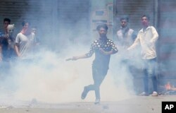 FILE - A Kashmiri Muslim protester throws back a teargas shell at Indian paramilitary soldiers in Srinagar, Indian-controlled Kashmir, July 10, 2016.