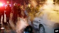 11月25日晚上,密蘇里州的弗格森一名警員上前查看遭一部冒煙的警車。有抗議者向警車投擲冒煙的裝置。