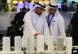 Men look at an architectural model of a housing development at the Cityscape Global exhibition, in Dubai, United Arab Emirates, Sept. 11, 2017.